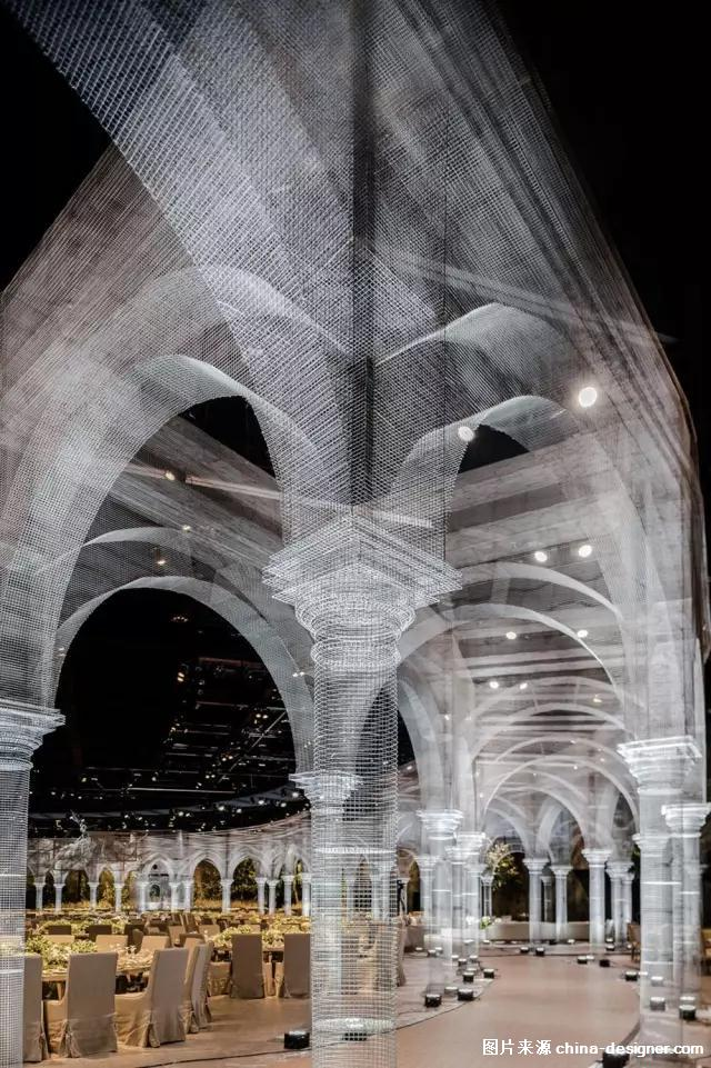 意大利艺术家 Edoardo Tresoldi 用金属丝构筑起一个巨大的网状结构 模拟古镇建筑特色 将空间转变成了光和透明的混合体 把历史遗迹通过网状结构重现出来    这些半透明的建筑 由一根根巨大的圆柱支撑搭建 连接成为宴席的长廊 此外在宴席中央的花坛上 还悬浮着一个巨大的半透明穹顶